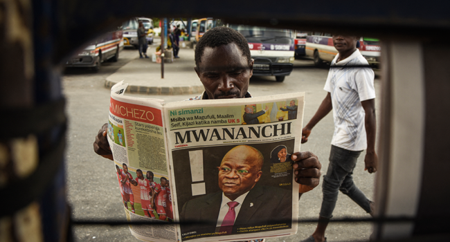 A man reads a newspaper with a headline announcing the death of Tanzania's President John Magufuli in Dar es Salaam, on March 18, 2021. AFP