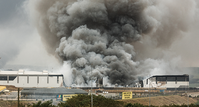 Smoke rises from a Makro building set on fire overnight in Umhlanga, north of Durban, on July 13, 2021 as several shops, businesses and infrastructure are damaged in the city, following four nights of continued violence and looting sparked by the jailing of ex-president Jacob Zuma. RAJESH JANTILAL / AFP